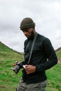Symbolbild für eine Persona-Beschreibung. Mann in sportlicher Kleidung mit Kamera in der Hand. Quelle: Unsplash